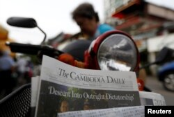 FILE - A woman buys the final issue of The Cambodia Daily newspaper at a store along a street in Phnom Penh, Cambodia, September 4, 2017. (REUTERS/Samrang Pring)