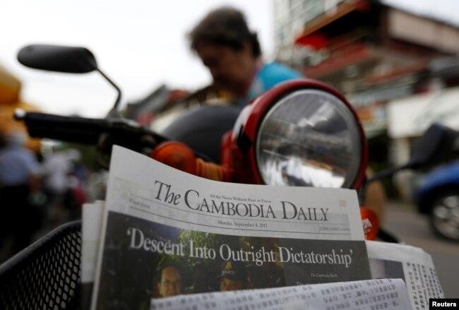 រូបភាពឯកសារ៖ ស្ត្រីម្នាក់ទិញកាសែត The Cambodia Daily ដែលបោះពុម្ពផ្សាយលេខចុងក្រោយ នៅតូបលក់កាសែតមួយក្នុងរាជធានីភ្នំពេញ ប្រទេសកម្ពុជា ថ្ងៃទី៤ ខែកញ្ញា ឆ្នាំ២០១៧។ (Reuters / Samrang Pring)