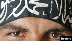 """A Free Syrian Army fighter in Aleppo wears a headband reading the Islamic declaration of faith, """"There is no God but God, and Mohammed is His Messenger."""""""