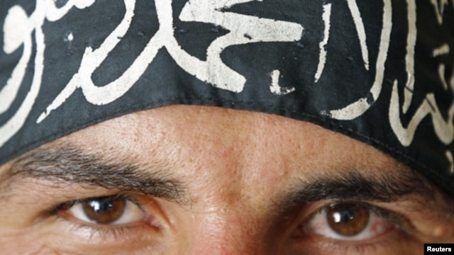 A Free Syrian Army fighter in Aleppo wears a headband reading the Islamic declaration of faith,