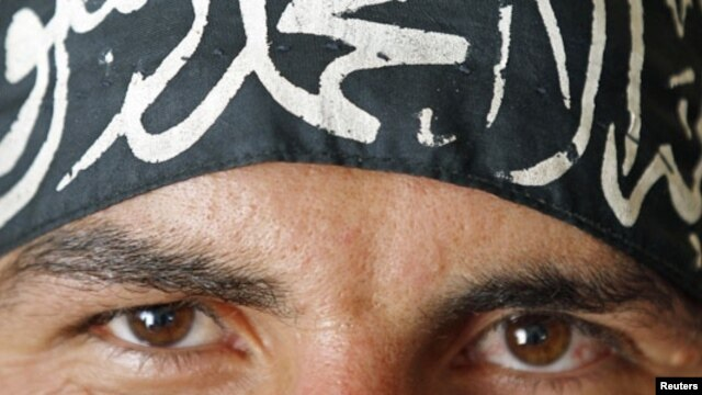 "A Free Syrian Army fighter in Aleppo wears a headband reading the Islamic declaration of faith, ""There is no God but God, and Mohammed is His Messenger."""