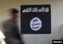 Un soldado pasa delante de una bandera negra generalmente usada por el grupo militante Estado Islámico.Foto de archivo.
