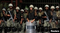Ranger soldiers stand guard against anti-government protesters rallying near the parliament building in Islamabad, Aug. 20, 2014.