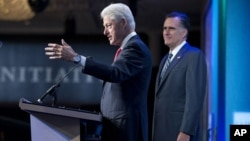 El expresidente Bill Clinton presenta a Mitt Romney, quien este martes habló ante el foro Iniciativa Global Clinton, en Nueva York.