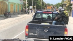 Cars are stopped on the road at Gressiers, Haiti.