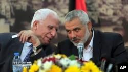 Pejabat senior Fatah, Azzam al-Ahmad (kiri) berbicara pada Perdana Menteri Hamas di Gaza, Ismail Haniyeh, dalam konferensi pers di Gaza, April 2014.