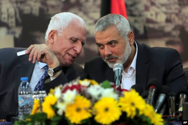 Senior Fatah official Azzam al-Ahmad, left, talks to Gaza's Hamas Prime Minister Ismail Haniyeh, during a press conference at Haniyeh's residence in Gaza Strip, Apr. 23, 2014.