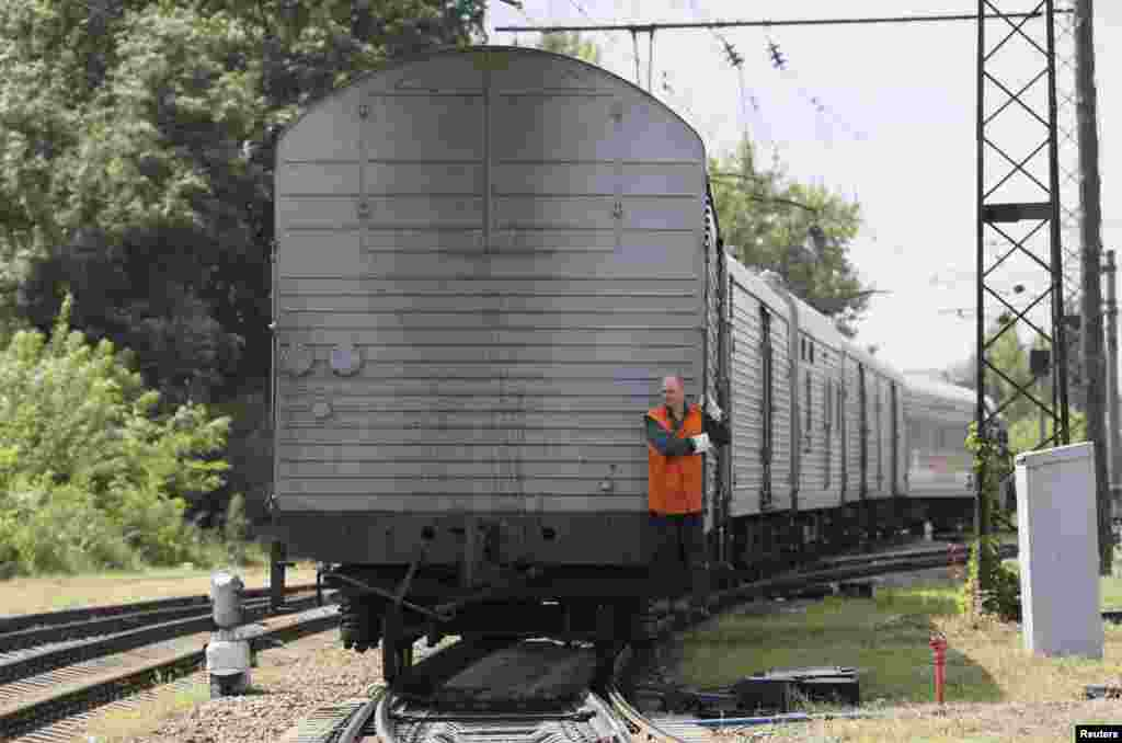 A guard rides on a train carrying the remains of victims of Malaysia Airlines MH17 downed over rebel-held territory in eastern Ukraine as it arrives in the city of Kharkiv, under Kyiv's control, July 22, 2014.