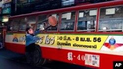 Seorang demonstran anti-pemerintah menyerang bus berisi orang-orang yang diduga mendukung pemerintah di Bangkok, Sabtu (30/11). (AP/Wason Wanichakom)