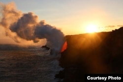 A wider view of the lava entering the ocean at sunset.