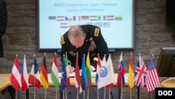 FILE - Gen. Martin E. Dempsey, chairman of the U.S. Joint Chiefs of Staff, signs a guestbook prior to starting a meeting at the NATO Cyber Defense Center of Excellence in Tallinn, Estonia, Sep. 14, 2015. (DoD photo by D. Myles Cullen/Released)