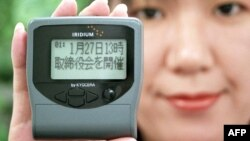 Karyawan Nippon Iridium, Nanae Saishoji, menunjukkan pager atau radio panggil buatan Iridium, 28 Desember 1998. (Foto: AFP/dok)