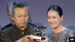 Đạo diễn Kim Ki-duk (trái) và diễn viên Cho Min-soo nhận giải thưởng Sư Tử Vàng cho phim Pieta tại Liên hoan phim Venice