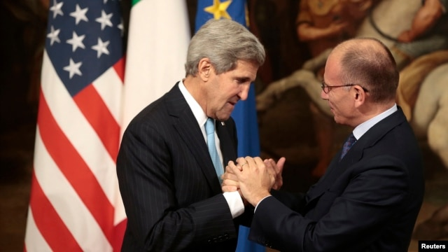 Italy's Prime Minister Enrico Letta (R) welcomes U.S. Secretary of State John Kerry during a meeting in Rome, Oct. 23, 2013.