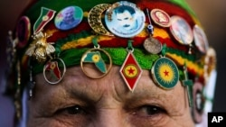 FILE - A woman wears Kurdish symbols and a sticker with a portrait of Abdullah Ocalan, the jailed leader of the rebel Kurdistan Workers' Party, or PKK, as she attends a protest of the visit of Turkish President Recep Tayyip Erdogan in Berlin, Germany.