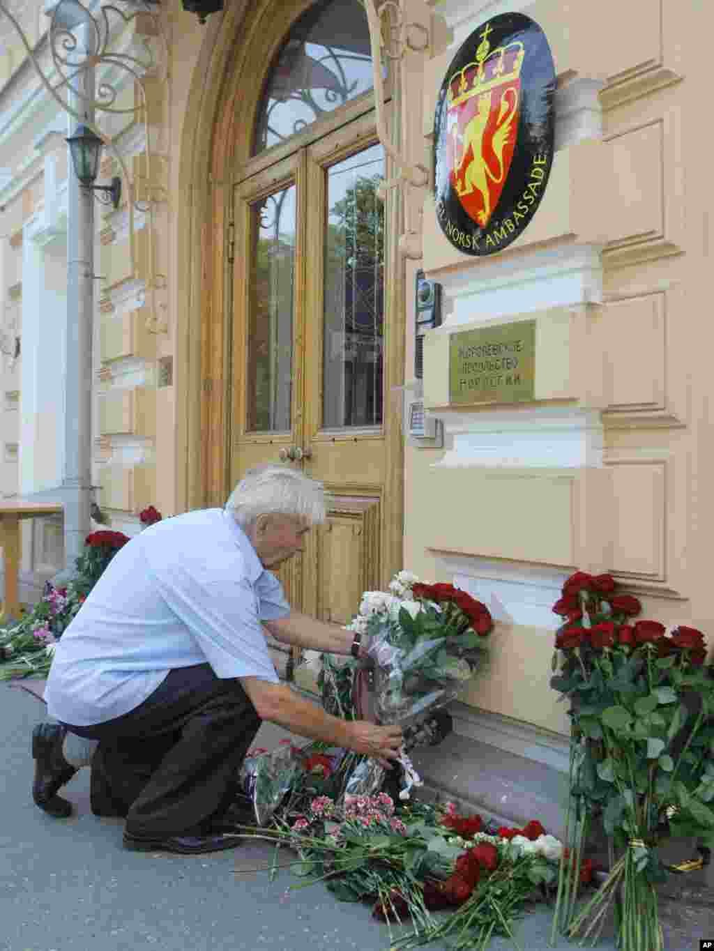 A man puts a flower tribute at the entrance in front of the Embassy of Norway in Moscow, Russia, in memory of the explosion's and shooting's victims. (AP)