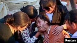 Các thành viên trong gia đình an ủi một phụ nữ mất con trong trận động đất mạnh ở phía tây tỉnh Cam Túc ngày 22 tháng bảy năm 2013.