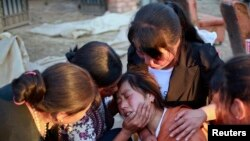 Para anggota keluarga menenangkan seorang perempuan yang kehilangan putrinya dalam gempa di provinsi Gansu, China.