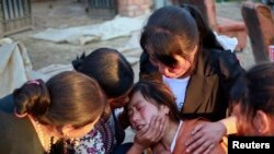 Depremde kızını kaybeden bir Çinli kadın ailesi tarafından teselli edilirken
