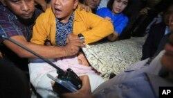 Para ajudan menutup wajah Ketua DPR Setya Novanto saat diangkut menuju Rumah Sakit Cipto Mangunkusumo di Jakarta, hari Jumat (17/11).
