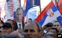 FILE - A Serbian Radical Party supporter holds a picture of Russian President Vladimir Putin during a pre-election rally in Novi Sad, Serbia, April 20, 2016. In a snap election days later, pro-EU Prime Minister Aleksandar Vucic's party kept its majority.