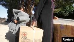 Pengungsi Suriah di desa Bekaa, Lebanon, membawa kardus berisi bantuan dari Palang Merah Internasional (ICRC). (Foto: Dok)