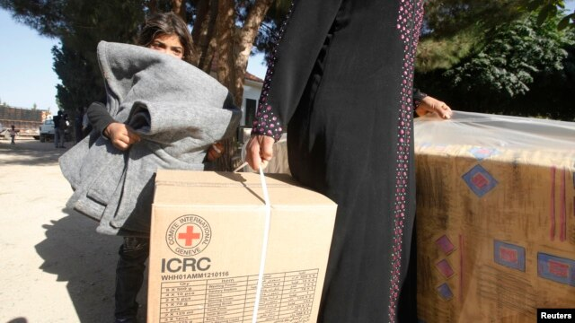 FILE - Syrian refugees in Lebanon's Bekaa Valley receive humanitarian aid from the ICRC, October 16, 2012.