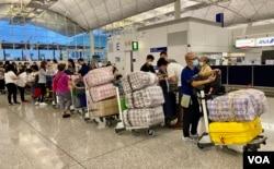 """英国LOTR安排届满前夕,7月18日晚香港国际机场出现移居英国的人潮,他们推着堆积如山的行李,港人惯用的大型""""红白蓝袋""""成为机场特别的风景。 (美国之音/汤惠芸)"""