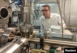 Professor John McGeehan, an X-ray Crystallographer at the University of Portsmouth, stands next to equipment at the Diamond Light Source, the UK national synchrotron, that he used to reveal the atomic structure of an enzyme.