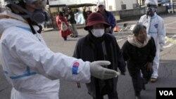 Socorristas continúan las labores de ayudar a los ciudadanos japoneses a realizar pruebas para detectar indicios de exposición a la radiactividad.
