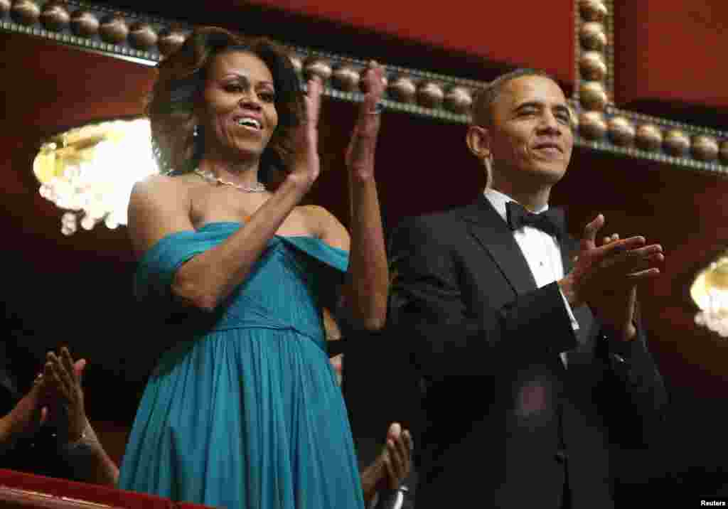 U.S. President Barack Obama and first lady Michelle Obama applaud the national anthem as they arrive in their box for the 2013 Kennedy Center Honors at the Kennedy Center in Washington, Dec. 8, 2013.