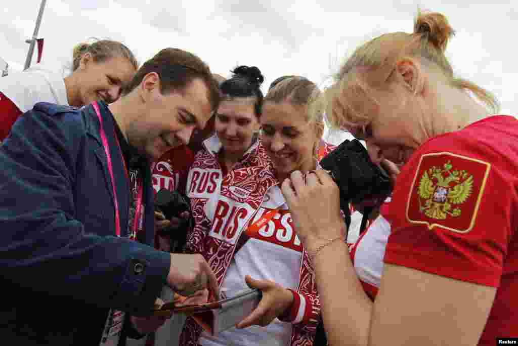 Russia's Prime Minister Dmitry Medvedev (L) meets with members of the Russian Olympic team as he visits the Olympic Village at the London 2012 Olympic Games in London July 28, 2012.