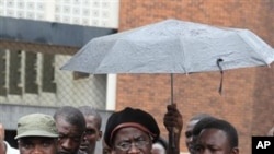 "Munyaradzi Gwisa, centre, talks to media as he leaves the magistrates courts in Harare, Wednesday, March 21, 2012. Gwisai, a human rights activist and five others were found guilty and made to pay a fine of $500 each and perform community service, for ""co"