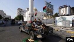 Rebeldes que patrullan las calles de Trípoli pasan sobre un retrato del fugitivo Gadhafi.