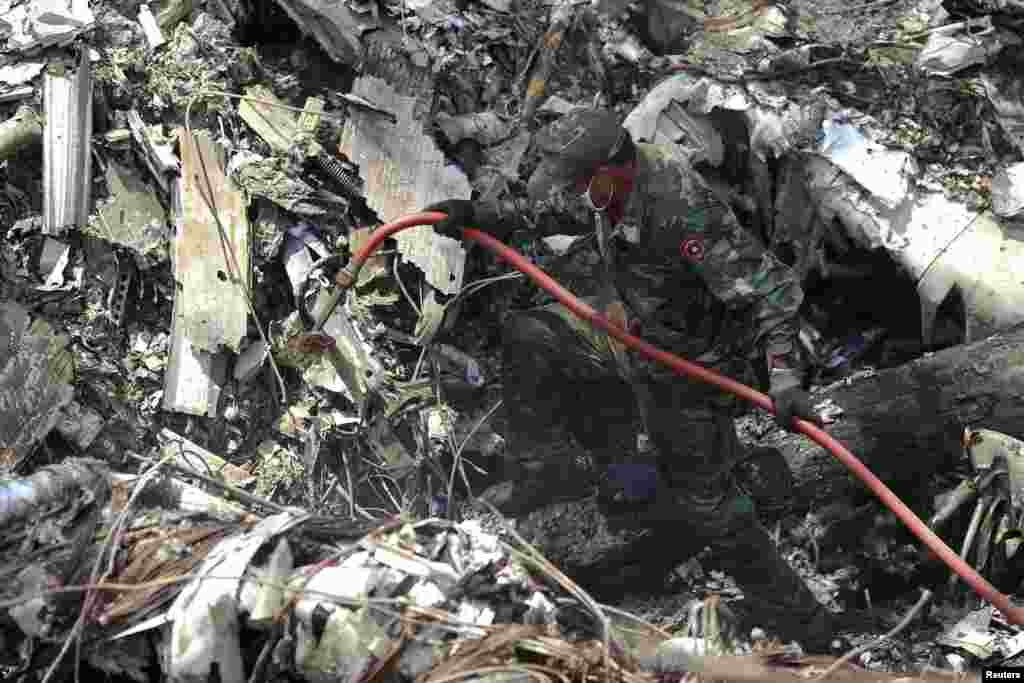 A rescue worker makes his way through the debris at an air force plane crash site near Nadee village, Xiang Khouang province, Laos, May 17, 2014.
