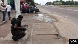 ເຈົ້າໜ້າທີ່ຮັກສາຄວາມປອດໄພ ຄອງໂກ ຄົນນຶ່ງກໍາລັງຍາມຢູ່ ຖະໜົນ ໄກ້ກັບສະຖານີໂທລະພາບ ທີ່ເມືອງຫລວງ Kinshasa.