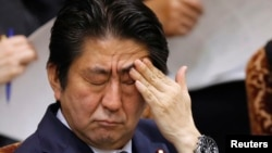 Japan's Prime Minister Shinzo Abe touches his face during an upper house committee session at the parliament...