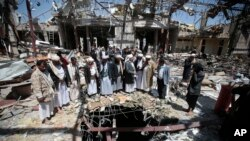 FILE- In this Oct. 13, 2016 file photo, members of the Higher Council for Civilian Community Organization inspect a destroyed funeral hall as they protest against a deadly Saudi-led airstrike on a funeral hall six days ago, in Sana'a, Yemen.