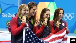 The United States team, Katie Ledecky, Allison Schmitt, Leah Smith and Maya DiRado, from left, hold up their gold medals after winning the women's 4x200-meter freestyle relay during the swimming competitions at the 2016 Summer Olympics, Thursday, Aug. 11, 2016.