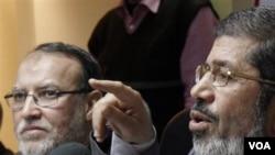 Para pemimpin Ikhwanul Muslimin, Essam el-Erian (kiri) dan Mohamed Morsi memberikan konferensi pers di Kairo (9/2).