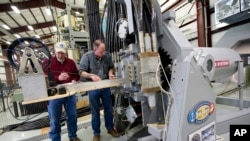 In this Thursday, Feb. 23, 2012, file photo provided by the U.S. Navy, Gary Bass, left, and Jim Poyner, from the Naval Surface Warfare Center, Dahlgren Division, take measurements after a successful test firing of an electromagnetic railgun prototype launcher.