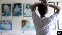 Tourist looks at portraits of former Khmer Rouge leaders, file photo.