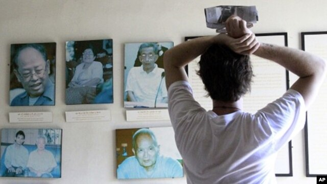 Tourist looks at portraits of former Khmer Rouge leaders Ieng Sary (L), 84, ex-foreign minister, his wife Ieng Thirith, 78, former minister of social welfare (2nd L), former prison chief Kaing Guek Eav (R), better known as Duch, former President Khieu Sa