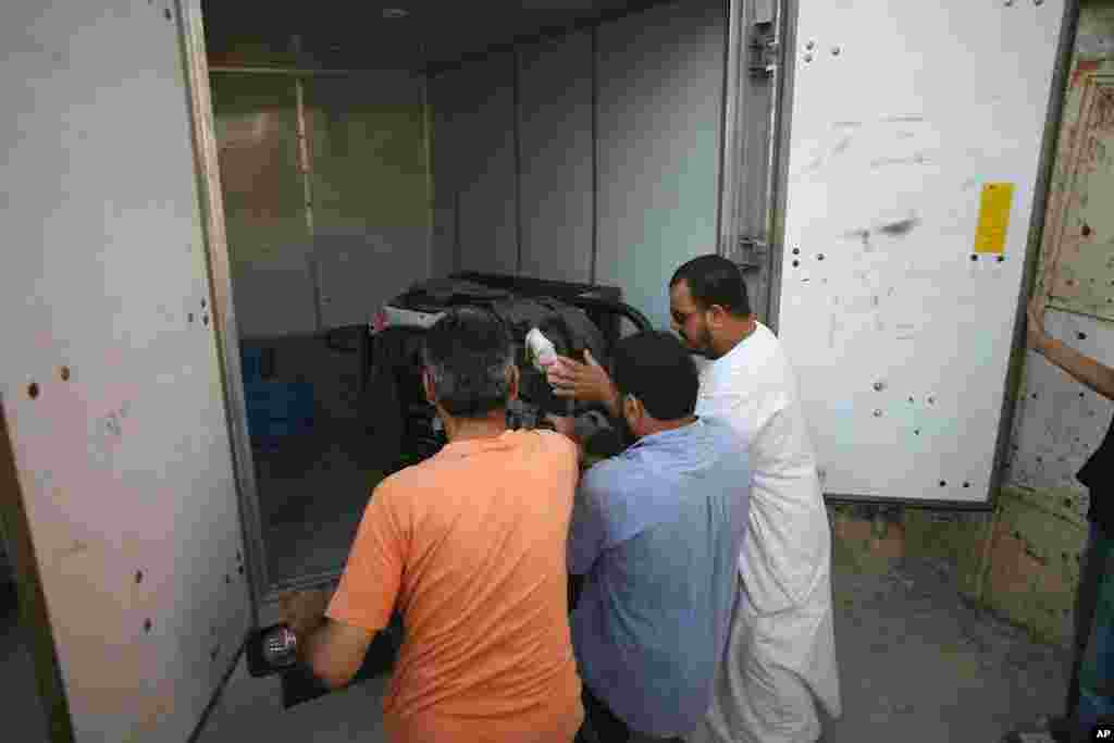 Tripoli residents unload a generator to pump water from a local mosque. (VOA Photo - J. Weeks)