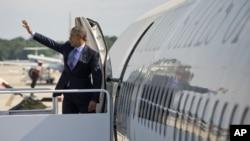 Presiden Barack Obama melambaikan tangan di atas pesawat Air Force One sebelum meninggalkan Pangkalan Udara Andrews, 20 Mei 2015, menuju New London, Conn.
