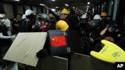 Para demonstran menggunakan berbagai benda untuk melindungi diri berusaha melewati stasiun kereta bawah tanah menuju ke kantor polisi di Hong Kong, 4 Agustus 2019. (Foto: AP)