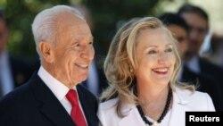 ປະທານາທິບໍດີຂອງ ອິສຣະແອລ Shimon Peres ຢືນຮຽກກັບທ່ານນາງ ຮິລແລຣີ ຄລິນຕັນ ລັດຖະມົນຕີການຕ່າງປະເທດສະຫະລັດ ກ່ອນຈະເຂົ້າພົບປະກັນ ຢູ່ກຸງ Jerusalem ໃນວັນທີ 16 ກໍລະກົດ, 2012 ມື້ນີ້