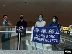 6月30日港版國安法實施前最後一次網民在中環置地廣場發起的和你Lunch示威,有人展示香港獨立旗幟。(美國之音湯惠芸)