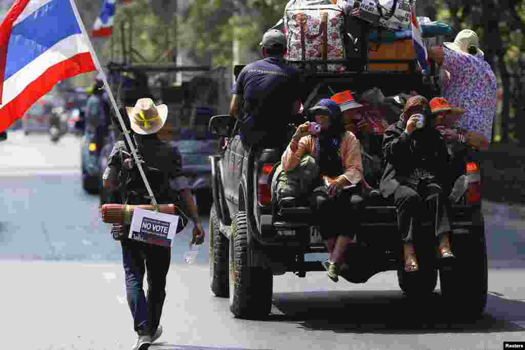 "An anti-government protester carrying a national flag, a guitar and a ""No Vote"" sign follows others moving from one protest camp to another in Bangkok Feb. 3, 2014."