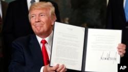 도널드 트럼프 미국 대통령이 14일 중국 기업의 미국 지적재산권 침해 행위를 조사하도록 하는 행정명령에 서명한 후 들어보이고 있다.